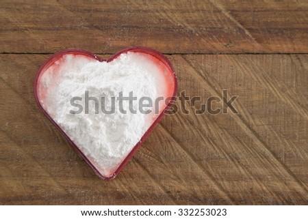 Soda, heart-shaped box. Wooden surface. - stock photo