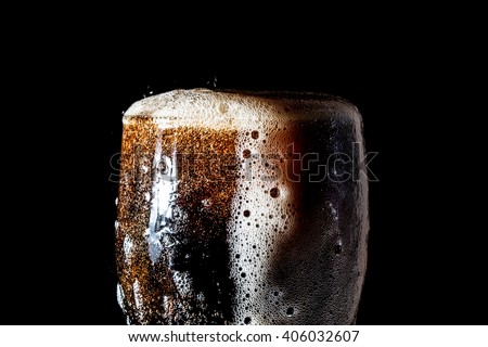 Soda large glass, overflowing glass of soda closeup with bubbles isolated on black background - stock photo