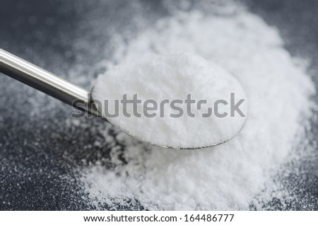 Sodium bicarbonate in a spoon - stock photo