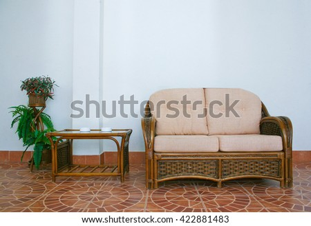 sofa and rattan table in an interior against wall - stock photo