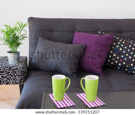 Sofa decorated with bright cushions, green plant and big cups on a table. - stock photo