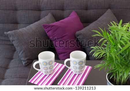 Sofa decorated with cushions, two cups on a table and green plant. - stock photo
