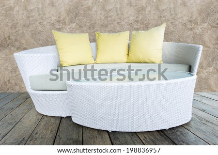sofa furniture weave bamboo stick chair with yellow pillows on wood and grunge concrete wall - stock photo