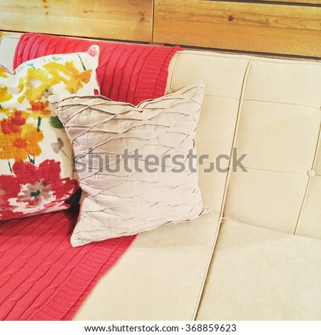 Sofa with pink throw and decorative cushions. - stock photo