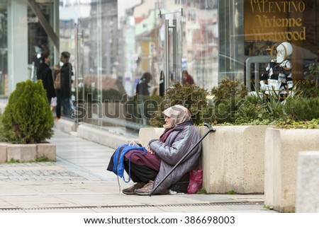Sofia, Bulgaria - February 27, 2016: A homeless beggar woman is begging at a street in front of a clothing boutique in Sofia. Bulgaria is still the poorest EU country. - stock photo