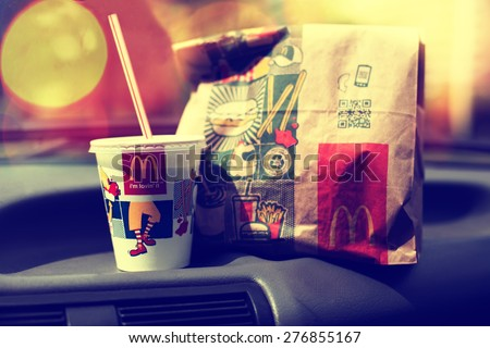 SOFIA, BULGARIA - MAY 9, 2015: McDonalds Mcdrive meal in vintage car, modern filtered look, abstract city bokeh background.Is the world's largest fast food chain, over 31,000 restaurants worldwide. - stock photo