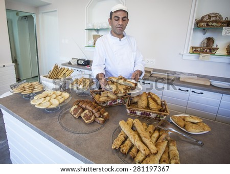 Sofia, Bulgaria - November 17, 2014: Gypsy baker shows freshly prepared bread, croissants, cookies, pancakes and pretzels at the restaurant for fast food in the city center. - stock photo