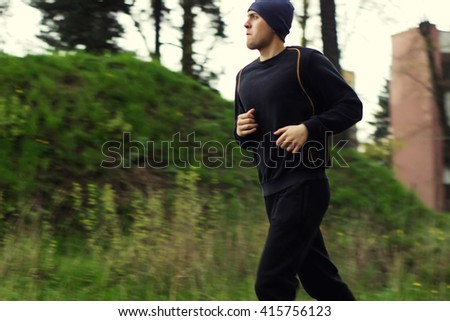 Soft and blur conception. Young man close up on a street in sportswear is engaged in running in cloudy weather - stock photo