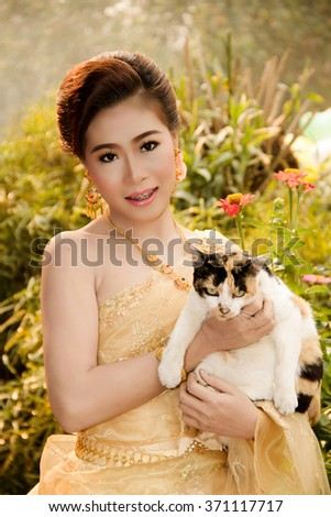 Soft Beautiful Thai women wearing typical Thai dress, identity culture of Thailand with cat - stock photo