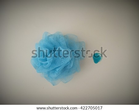 Soft blue bath puff or sponge with rode handle with blue wash gel - stock photo
