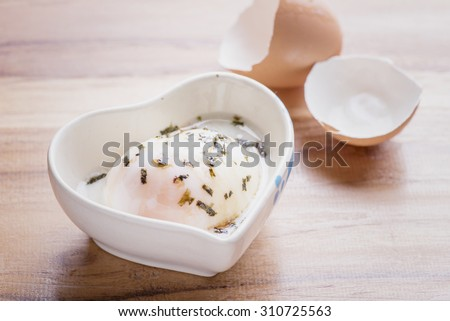 Soft-boiled egg or Onsen egg with eggshell on wooden table - stock photo