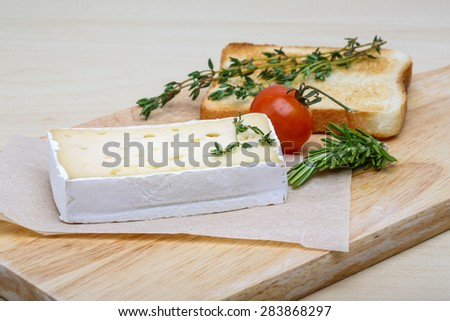 Soft brie cheese with rosemary, thyme and toast bread - stock photo