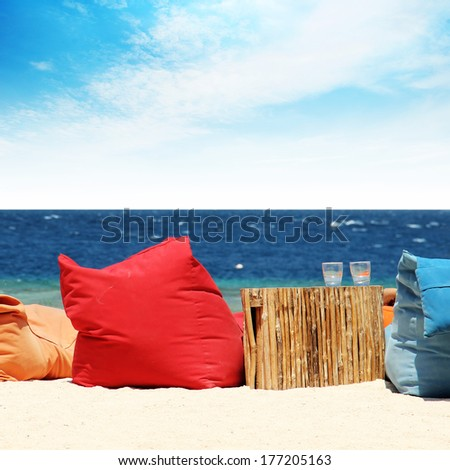 soft chairs on the beach overlooking the ocean - stock photo