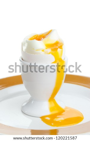 Soft-cooked egg in cup with yolk running out - stock photo
