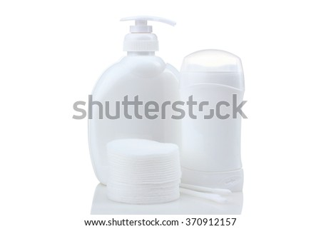 soft cotton pads neatly folded stack of cotton swabs and about cosmetic container with liquid soap and a deodorant stick container. Design white plastic bag isolated on white background - stock photo