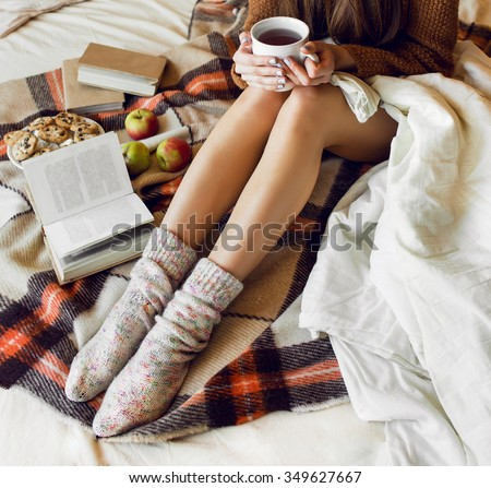 Soft cozy photo of slim tan woman in warm sweater and woolen socks  on the bed with  book  in hands, top view point.  Checkered plaid near  a plate of oatmeal cookies. Fall or winter time  concept.  - stock photo