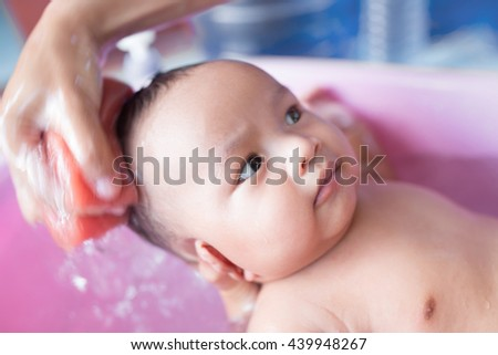Soft focus Cute Asian male baby in a tub. 3 months baby boy is happy. Healthy baby boy. Blurred background. - stock photo