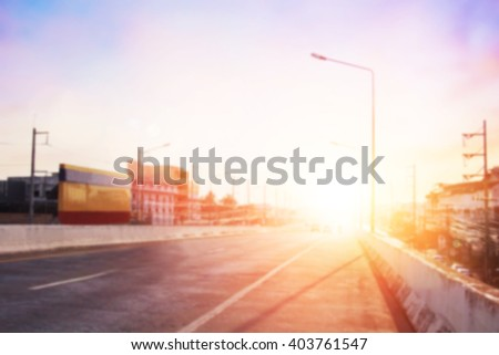 Soft focus expressway asphalt road with car in a city landscape at sunrise. Driving on a Highway with colorful sky. Blurred of peaceful landscape sunset. Abstract blur glowing bokeh colorful. - stock photo