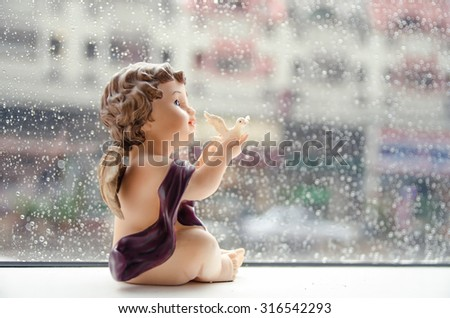 Soft focus for Little Cupid holding white dove resin in rain background. - stock photo