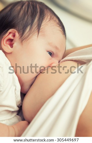 Soft focus image of newborn baby breastfeeding - stock photo