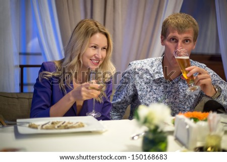 Soft focus on a beautiful couple in a restaurant with glasses in hands  - stock photo