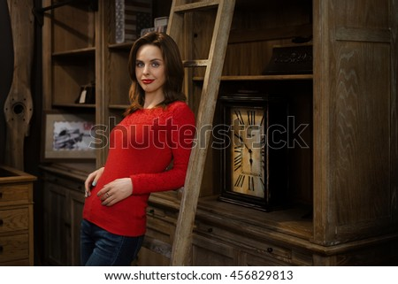 Soft focus portrait of attractive young lady standing near ladder. Image taken in low light conditions at wide open aperture and contain noise and soft focus. - stock photo