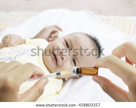 Soft focus Syringe with vial on hands of a nurse,doctor administer the injection and blurred background of asian baby on the towel is crying. - stock photo