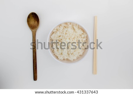 Soft focus White rice in bowl and chopsticks and a spoon on a white background / top view. - stock photo