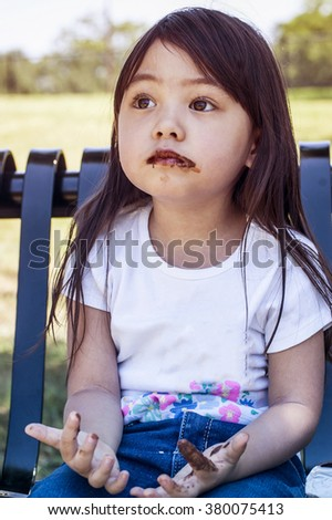 Soft focused filter colored and closed up a little girl tasting eating chocolate and bread sticks on metal bench at public park - stock photo