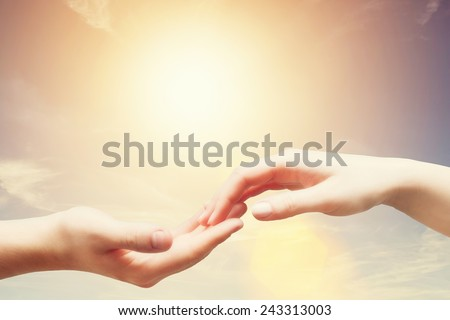 Soft, gentle touch of man and woman against sunny sky with flare in vintage mood. Love, connection, help concepts. - stock photo