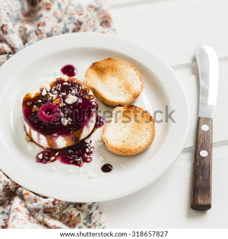 soft goat cheese with berry sauce, balsamic vinegar and nuts - a delicious appetizer with wine, on a white plate on a light wooden background - stock photo