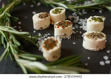 soft goat cheese with rosemary on a gray background - stock photo