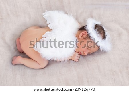Soft image of cute newborn baby sleeping on grey background covered with white angel's wings and halo nimbus made of feathers, focus on close eye, ear, hear, halo and plumage - stock photo