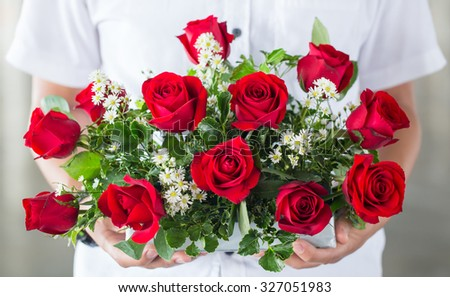 soft light tone with male hand giving bouquet of red roses - stock photo
