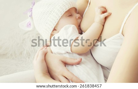 Soft photo mother feeding breast her baby at home  - stock photo