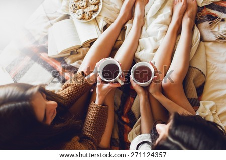 Soft photo of two  sisters  on the bed with old books and cup of tea in hands wearing cozy sweater , top view point. Two best friends enjoying morning. - stock photo