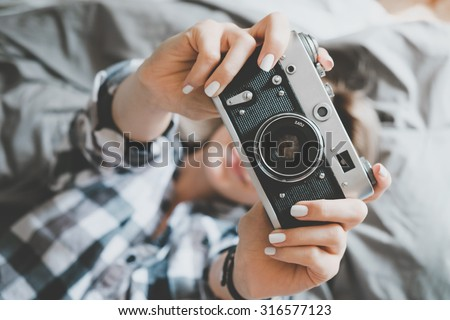 Soft photo of woman in checkered shirt taking a photo, top view point - stock photo