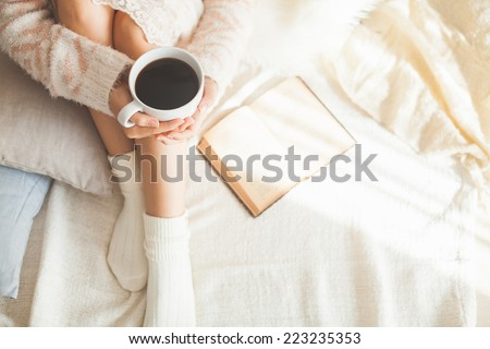 Soft photo of woman on the bed with old book and cup of coffee in hands, top view point - stock photo