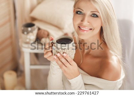 Soft photo of woman on the bed with old book and cup of coffee in hands, top view point. Cozy, comfy, soft  Home portrait of beautiful young woman, selective soft focus - stock photo