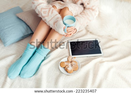 Soft photo of woman on the bed with tablet and cup of milk in hands, top view point - stock photo