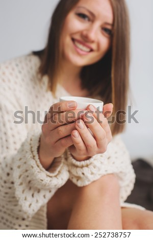 Soft photo of woman with  cup of coffee in her hands.  Selective soft focus  - stock photo