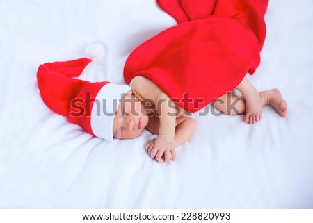 Soft portrait of newborn baby boy kid in red santa claus hat, sleeping on white background. Focus on face and hands. Merry christmas and happy new year greeting card. - stock photo