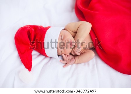 Soft portrait of newborn baby boy kid in red santa claus hat, sleeping on white background. Merry christmas and happy new year greeting card. Focus on baby's nose and eyes - stock photo