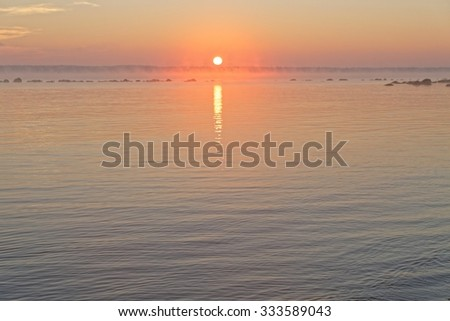 Soft romantic sunrise with pastel colors over the calm Baltic sea - stock photo