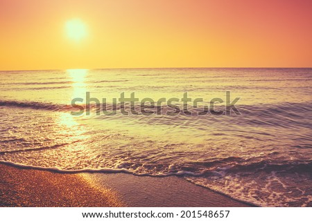 Soft Sea Ocean Waves Wash Over Golden Sand Background. Sunset, Sunrise, Sun. Toned like instant photo - stock photo