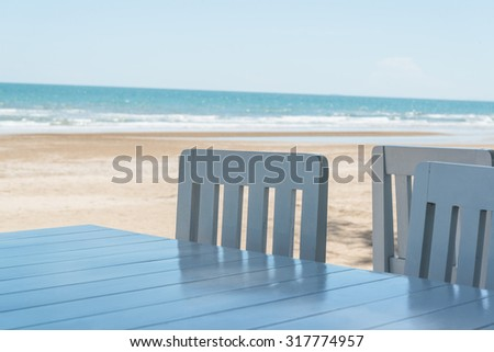 Soft shot of blue chairs and table on the tropical sand beach background - stock photo