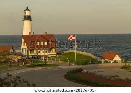 Soft sunlight on the most popular lighthouse of Maine; Portland Head Light along rugged Atlantic Coast of Southern Maine. - stock photo