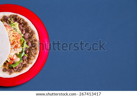 Soft taco with savory filling and vegetables served on a red plate over a blue background with copy space, overhead view - stock photo