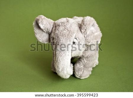 Soft toy a plush elephant on green background - stock photo