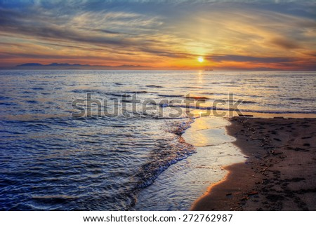 Soft waves breaking onto sandy beach shore at sunrise - stock photo